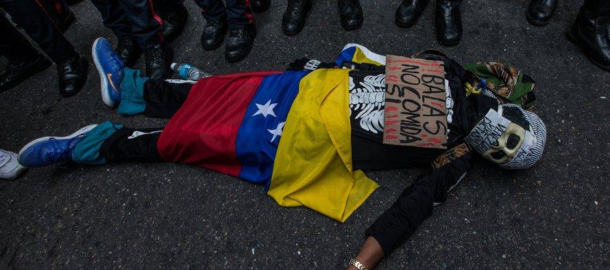 """Un manifestante protesta frente a un bloqueo policial con carteles que dicen: """"Balas no...."""