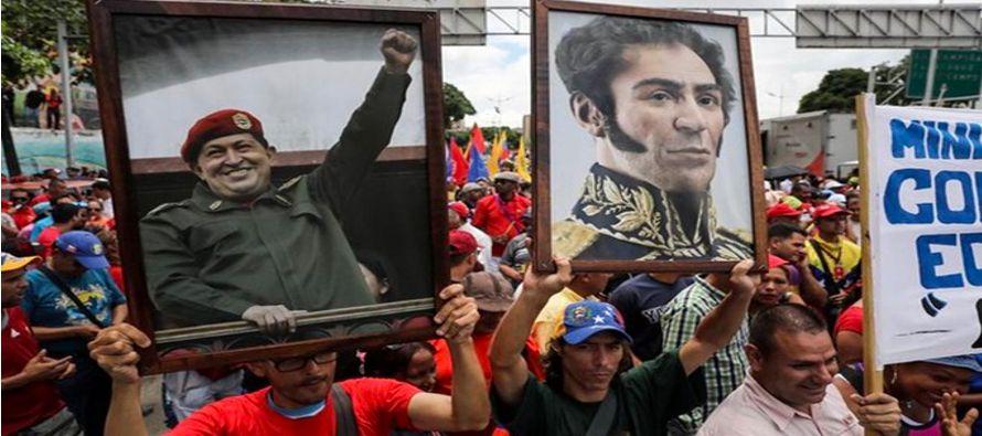 Cargando un gran retrato del fallecido presidente Hugo Chávez y del libertador Simón...