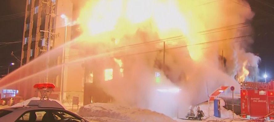 Las imágenes de televisión mostraban un edificio de tres plantas en llamas, con...